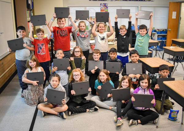 Students at Hoover hold up their Chromebooks