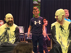 Student with teachers and principal covered in slime