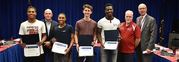 Neshaminy HS track team relay members hold up certificates at a Board meeting