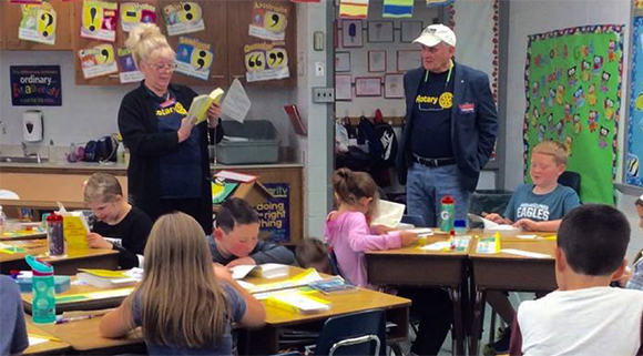 Rotarians handing out dictionaries at Buck Elementary