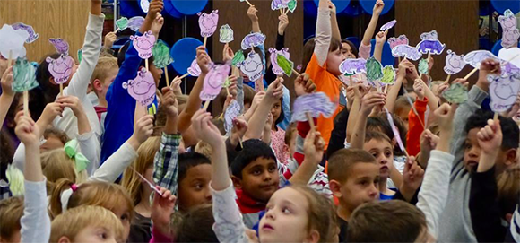 Students hold signs at author assembly