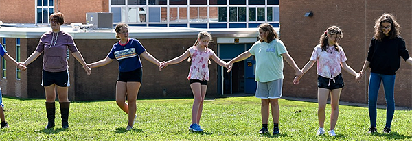 Students holding hands during a team-building exercise