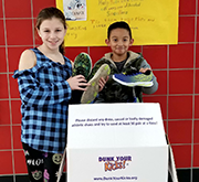 Students pose with Dunk Your Kicks donation box